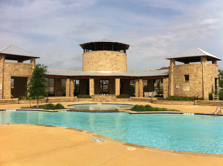 pool with large brick pool house