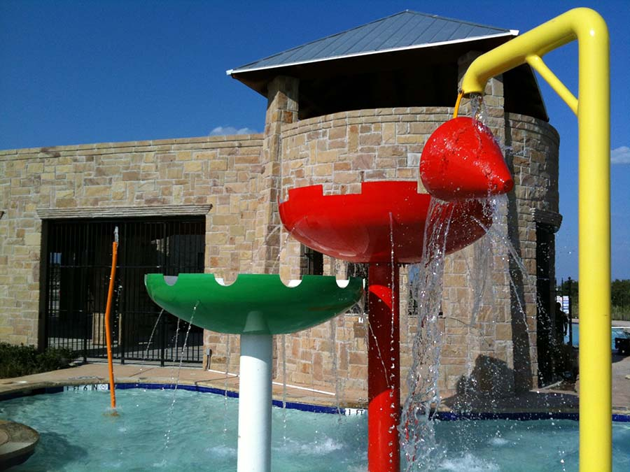 water features of a pool with a brick pool house on the background