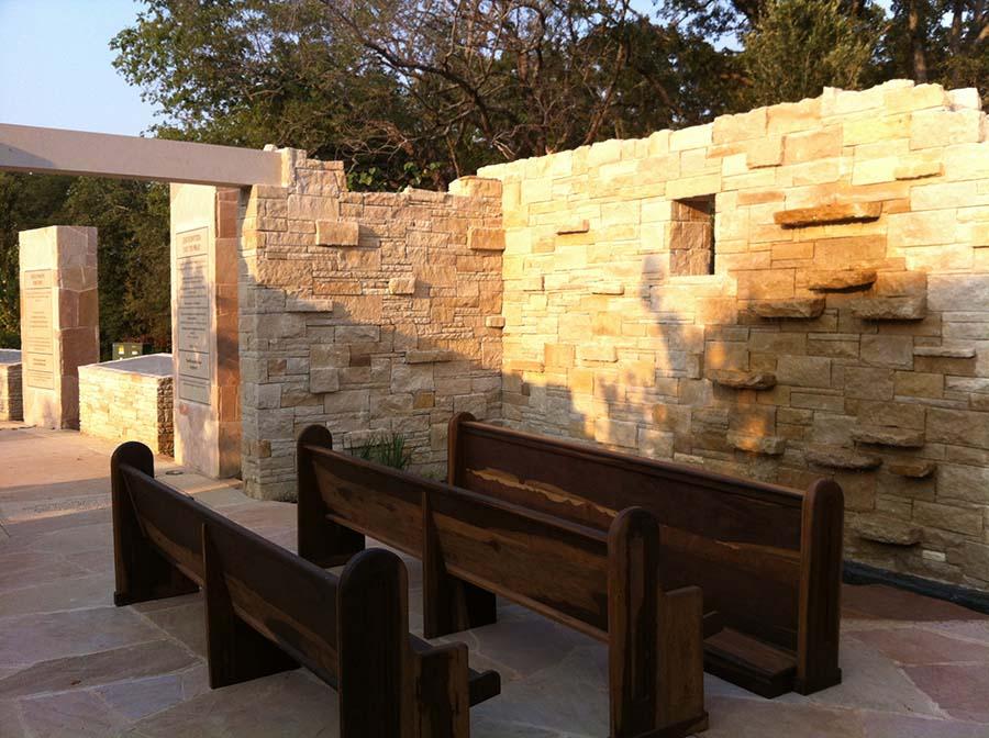 church pews facing a brick wall