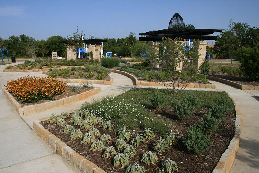portion of a park with landscaping and plants in neat rows