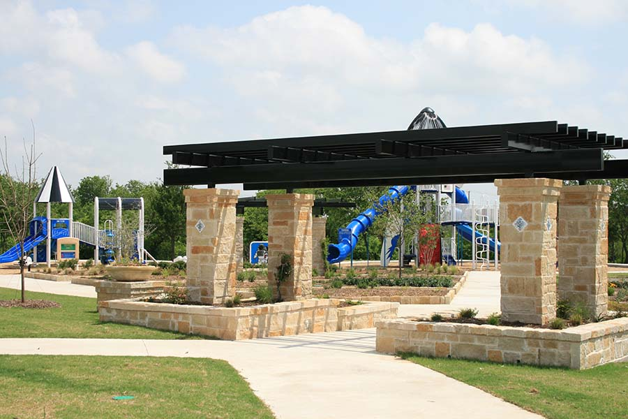entrance to a park with brick columns and a playground visible in the background