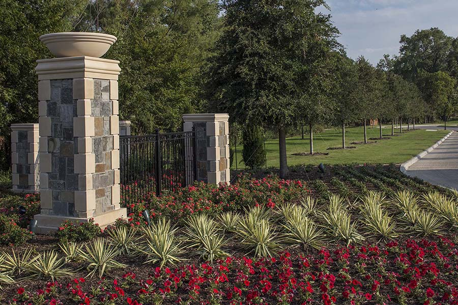 portion of a park with brick columns, black metal fences, and rows of ornamental plants