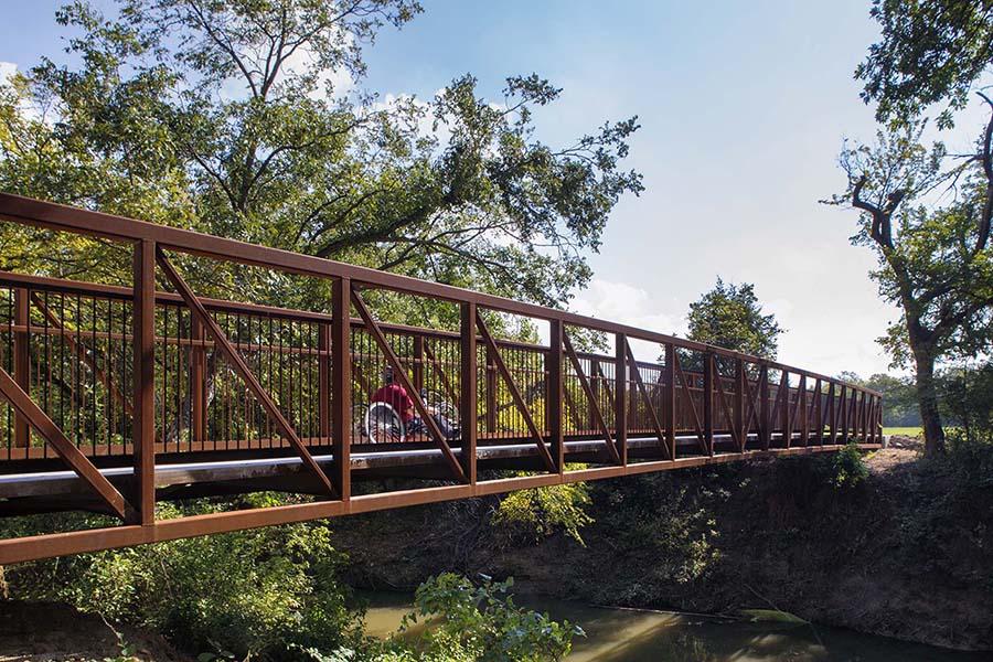 rust-colored bridge crossing a small creek