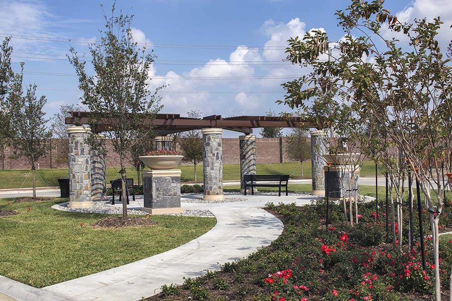 shaded portion of park with brick columns and benches