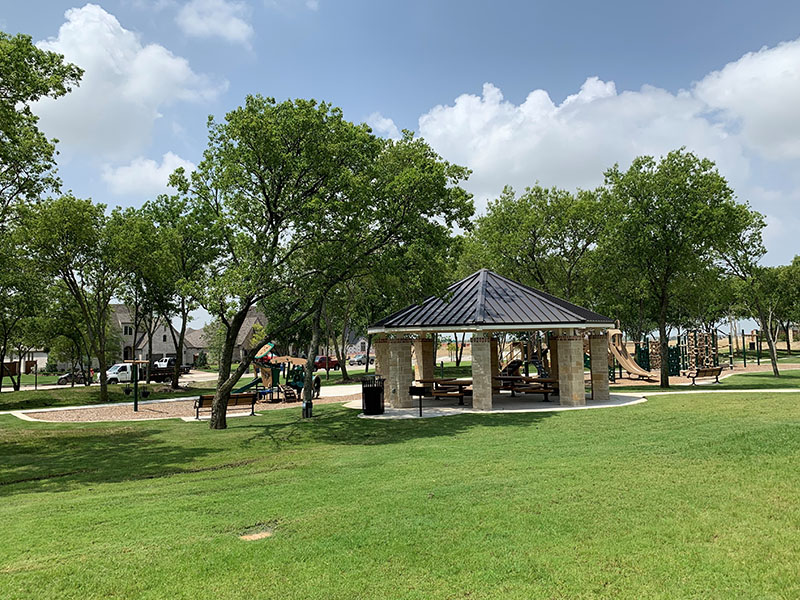 park grounds with green grass and a gazebo