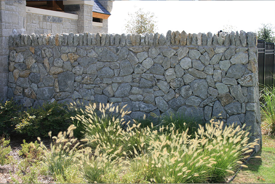 wall with gray stones and flowering plants in front