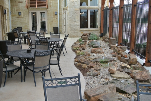 hall with chairs and tables and a landscaped rocky segment